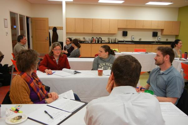 Five instructors discuss their teaching at tables during a WAC discussion event